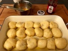 Buchteln mit Preiselbeerfüllung - in Butter getunkt in die Form setzen